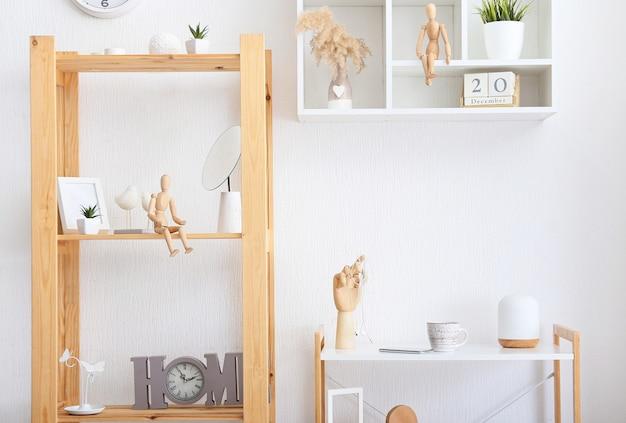 Стильный интерьер комнаты со столом и стеллажом и полками у светлой стены