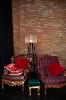 ヴィンテージのアームチェアと赤レンガの壁のあるスタイリッシュなインテリア。フロアランプ付きの居心地の良い装飾が施されたリビングルーム。リビングルームのロフトスタイル
