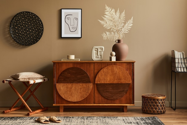 Стильный интерьер с дизайнерским деревянным комодом, табуретом, сухоцветами в вазе, уникальным декором, ковром, рамой и элегантными личными аксессуарами. современная гостиная в классическом доме.