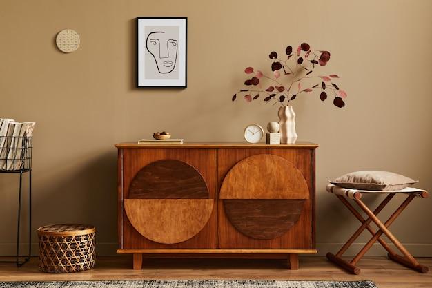Стильный интерьер с дизайнерским деревянным комодом, табуретом, сухоцветами в вазе, уникальным декором, ковром, рамкой для макета плаката и элегантными личными аксессуарами.