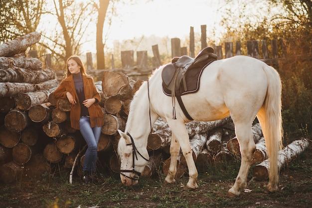Стильный жокей стоит рядом с белой лошадью, ест траву