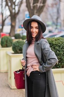 長い灰色のコート、公園の街の通りを歩いて帽子でスタイリッシュなうれしそうな若い女性。豪華な服、ファッショナブルなモデル、笑顔、陽気な気分、エレガントな外観。
