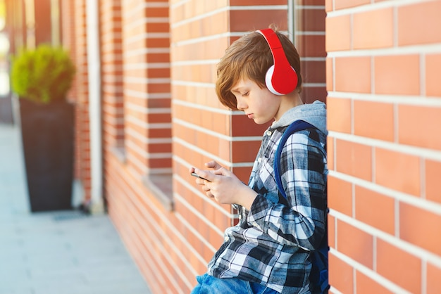 Stylish kid boy with headphones using phone at city street. young boy plays online game at smartphone. preteen boy listens to the music on smart phone