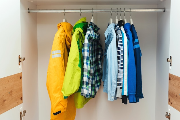 Stylish kids clothes in white wardrobe closet. kids clothing on hangers in the closet.