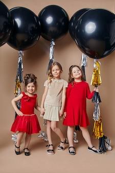 Stylish kids in evening dresses celebrating