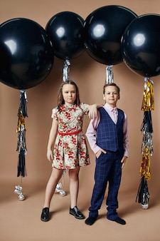 Stylish kids in evening dresses and costumes celebrating the first day of school