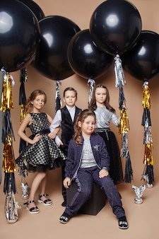 Stylish kids in evening dresses and costumes celebrating the first day of school.