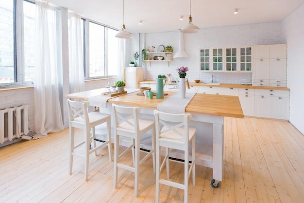 대형 높은 창문이있는 트렌디하고 현대적인 복층 아파트의 밝은 색상의 세련된 주방.