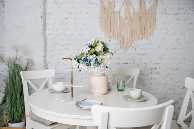 白、パステルカラーのスタイリッシュなキッチン。スタイルのミニマリズム。花、白いテーブル、植物、グラス、皿、皿と花瓶。白い家具、テーブル、レンガの壁とトレンディなインテリア。ロフトアパート