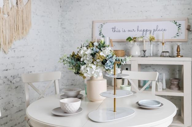 白、パステルカラーのスタイリッシュなキッチン。スタイルのミニマリズム。花、白いテーブル、植物、グラス、皿、皿と花瓶。白い家具、テーブル..ロフトアパートのデザインとトレンディなインテリア。