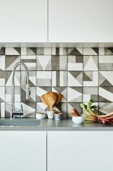 현대적인 아파트의 세련된 주방 인테리어 디자인에는 목재 주방 액세서리가 있는 작업 공간이 있습니다. 창의적인 벽. 최소한의 스타일과 식물 사랑 개념. 세부.