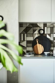 현대적인 아파트의 세련된 주방 인테리어 디자인에는 목재 주방 액세서리가 있는 작업 공간이 있습니다. 창의적인 벽. 최소한의 스타일과 식물 사랑 개념.