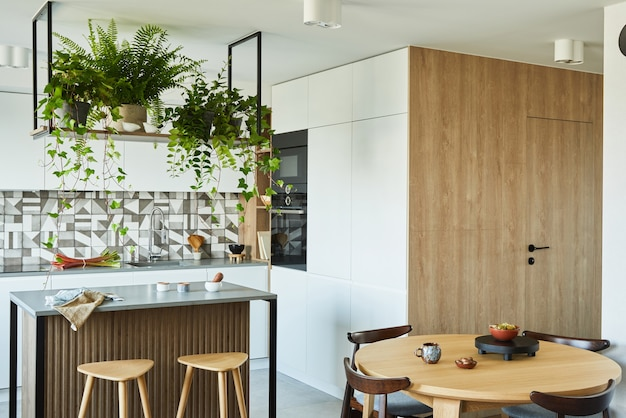 Stylish kitchen interior design with dining space. workspace with kitchen accessories on the back ground. creative walls with woode pannels. minimalistic style an plant love concept.