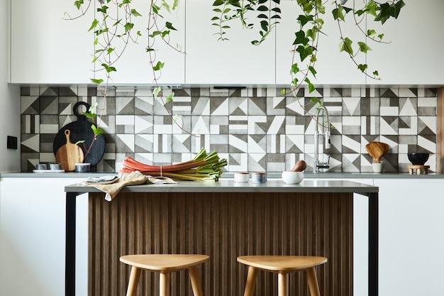 Стильный дизайн интерьера кухни с обеденной зоной. рабочее пространство с кухонными принадлежностями на заднем плане. креативные стены. минималистичный стиль концепция любви растений.
