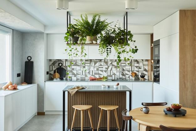 Стильный дизайн интерьера кухни с обеденной зоной. рабочее пространство с кухонными принадлежностями на заднем плане. креативные стены с деревянными панелями. минималистичный стиль концепция любви растений.