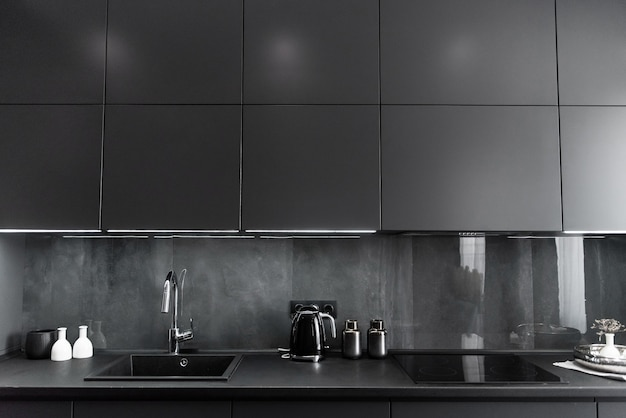 Stylish kitchen interior in grey and black colors