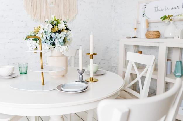 スタイリッシュなキッチン。花、白いテーブル、キャンドル、グラス、皿、皿と花瓶。白い家具、テーブル、レンガの壁とトレンディなインテリア。ロフトアパートのデザイン。プロヴァンス風のキッチン。