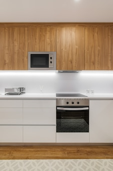 Stylish kitchen with modern furniture in white color with wooden cupboards and combined floor of til...