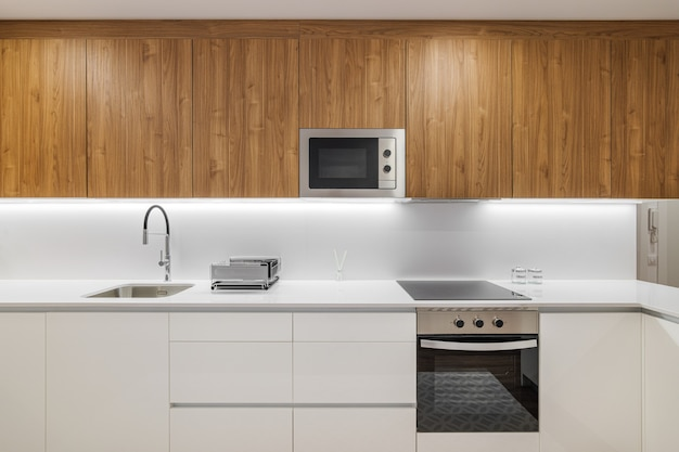 Stylish kitchen with modern furniture in white color with wooden cupboards for kitchenware contempor...