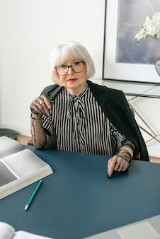 줄무늬 블라우스 장갑과 재킷을 입은 세련된 여성 보스는 사무실의 탁자에 앉아 있다
