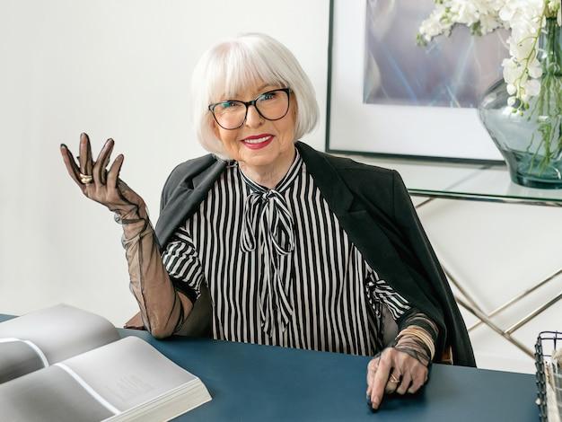Стильная дама-босс в полосатой блузке, перчатках и куртке сидит за столом в своем офисе