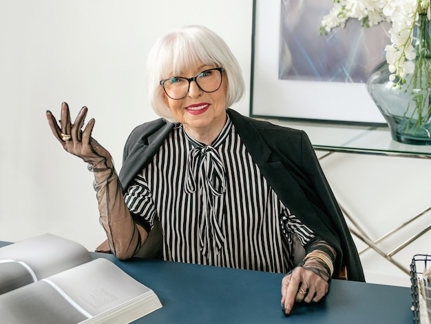Stylish lady boss in striped blouse gloves and jacket sitting by the table in her office
