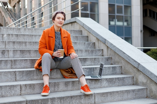 Stylish lady in bright orange coat in a city scene, using a laptop computer and working on it during a break. outdoors technology. drinking coffee, tea, cocoa