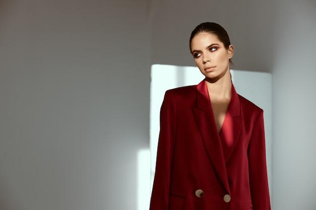 彼女の顔に明るい化粧をした赤いジャケットのスタイリッシュな女性