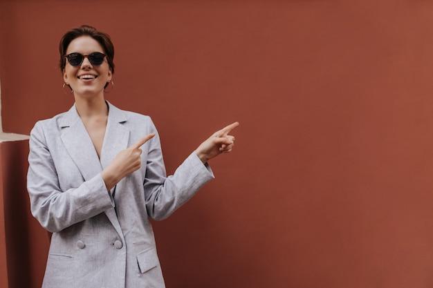 テキストの場所を指している灰色のスーツとサングラスのスタイリッシュな女性。特大のジャケットを着た陽気な短髪の女性は、外で広く笑っています