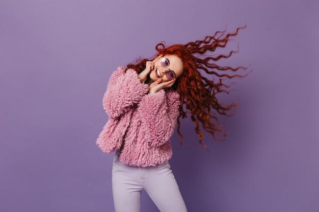 シープスキンのコートを着たスタイリッシュな女性、ライラックの空間で笑顔で髪を弾くスキニーパンツ。