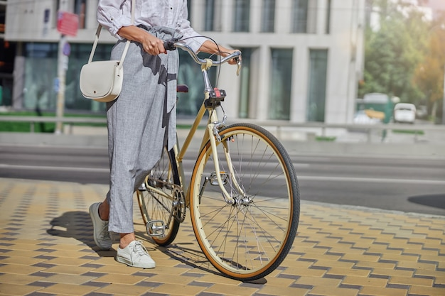 화창한 날 도시 거리의 아스팔트 위에 서서 도시 자전거의 핸들을 잡고 있는 흰색 옷을 입은 세련된 여성
