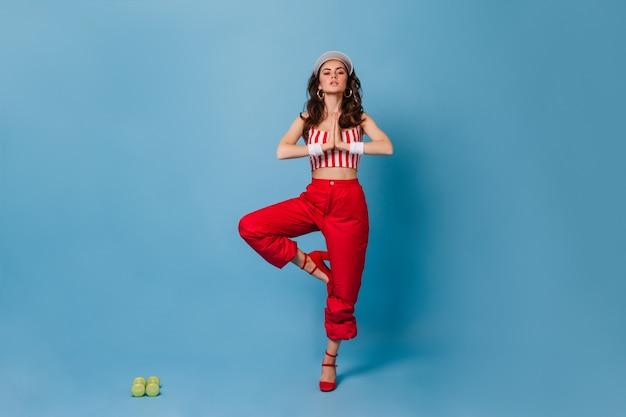 Elegante signora in pantaloni rossi e top ritagliata a strisce in piedi nella posa dell'albero sulla parete blu con manubri verdi