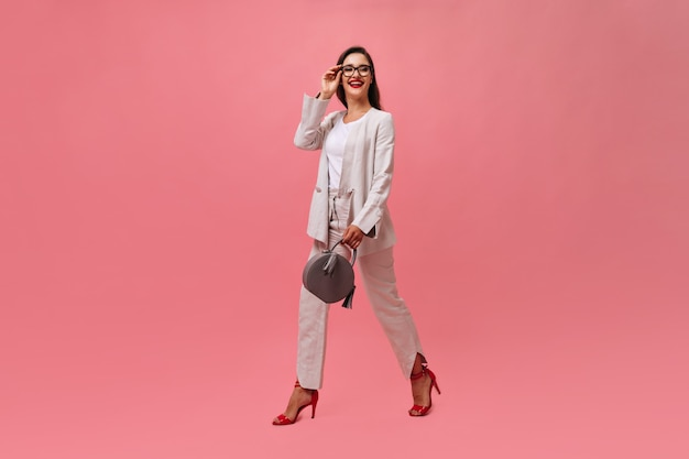 Stylish lady in suit holds handbag and walks on pink background.  business woman with dark hair with bright red lips and stylish heels smiling.