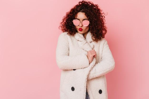 Signora alla moda in cappotto di pelliccia oversize bianco soffia bacio. ritratto di donna riccia in occhiali da sole sullo spazio rosa.