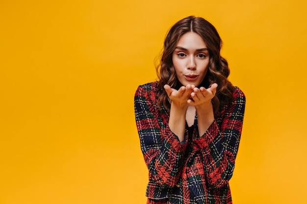 Stylish lady with wavy hair in striped jacket blowing kiss on isolated wall