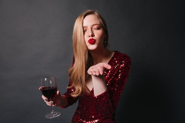 Elegante signora con bicchiere di vino che invia un bacio d'aria. studio shot di ragazza bionda in abito rosso, bere vino alla festa.
