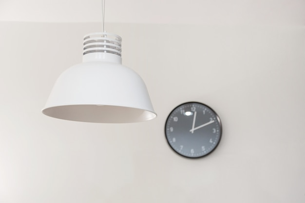 Stylish lamp and clock on wall.