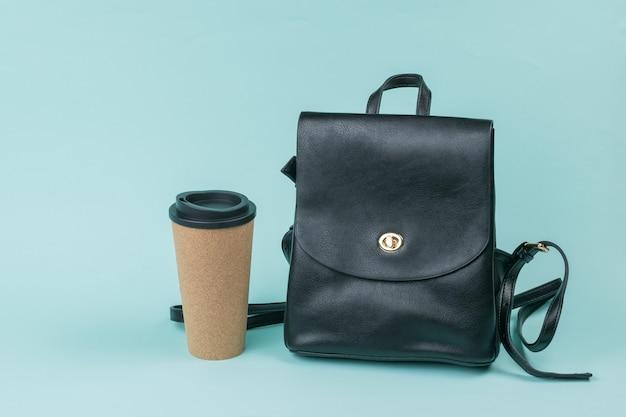 スタイリッシュな革のバックパックと青い背景のコーヒーと紙コップ。ライフスタイル。