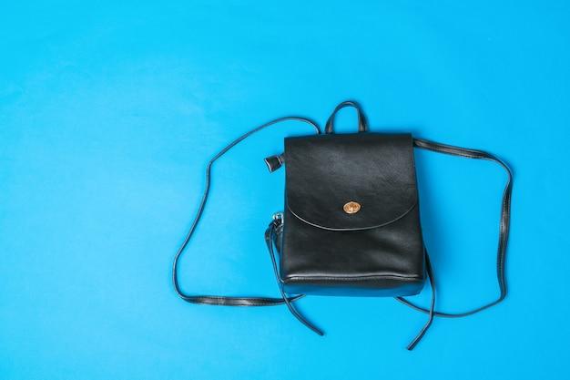 Стильный кожаный рюкзак на синем фоне. популярный вид сумок.
