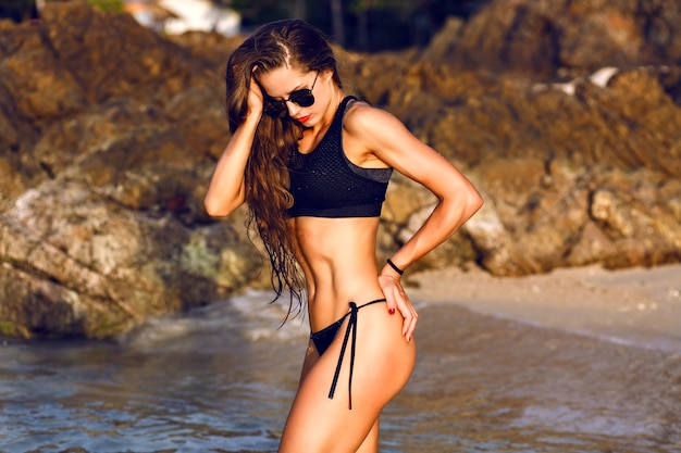 Stylish lifestyle summer tropical portrait of stunning fit slim woman, enjoy her vacation at the beach, relaxing luxury atmosphere. healthy lifestyle.