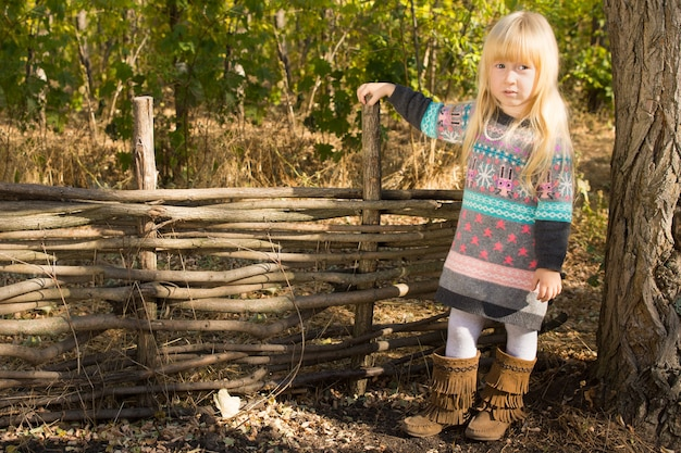 Stylish little blond girl posing next to a rustic wooden fence of interlaced sticks in her patterned jumper and leather boots