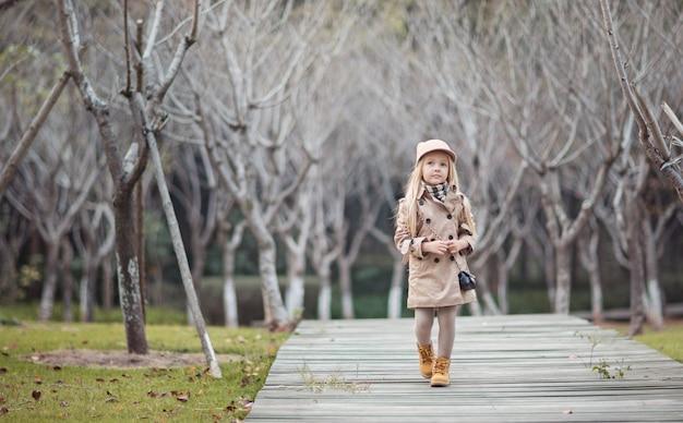 Stylish little blonde girl walking in autumnal park