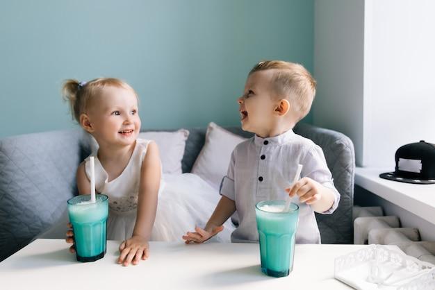 スタイリッシュな男の子と女の子、ミルクセーキを飲む子供たちのカフェ