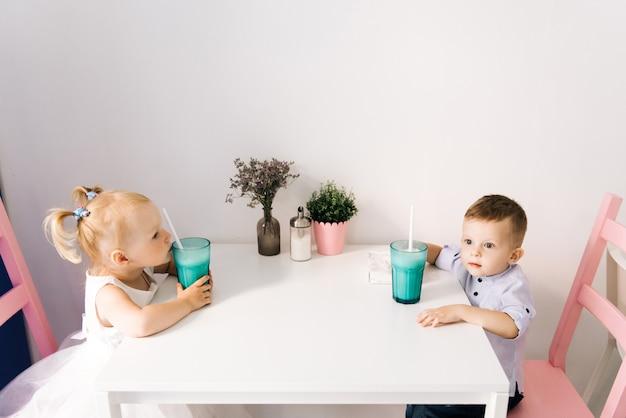 スタイリッシュな男の子と女の子、ミルクセーキを飲む子供たちのカフェ Premium写真