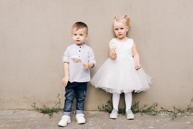 スタイリッシュな男の子と女の子の手にキャンディメレンゲと灰色の壁に
