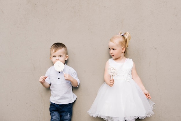 Stylish little boy and girl on a gray background with candy meringues in their hands