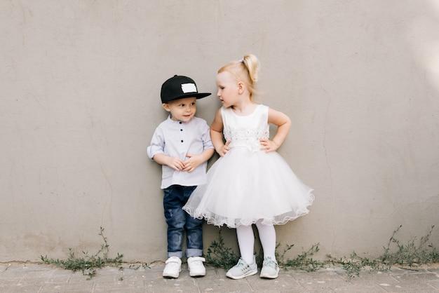 Stylish little boy and girl on grey background