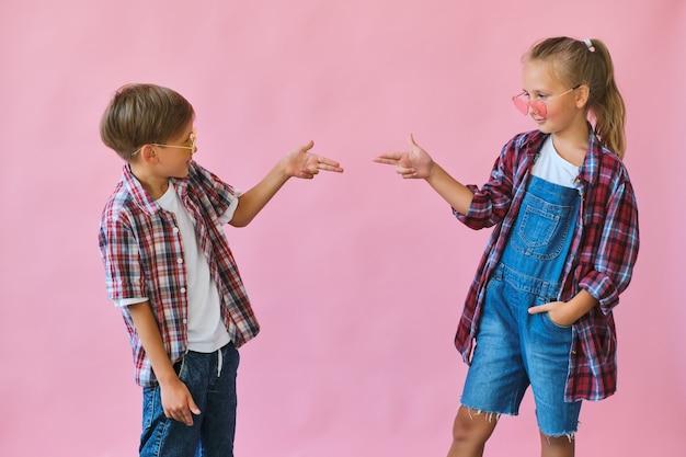 Стильная маленькая девочка и мальчик в цветных солнцезащитных очках, одетых в клетчатые рубашки
