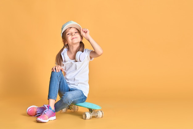 Stylish little girl child girl in casual with skateboard over yellow wall