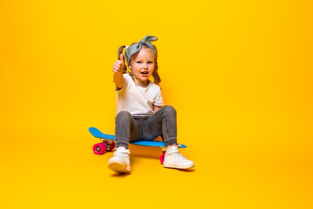 Stylish little girl child girl in casual with skateboard over yellow wall.